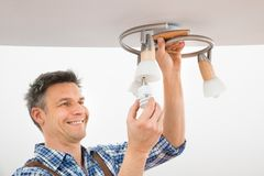 technician-fixing-light-ceiling-portrait-male-electrician-54962827